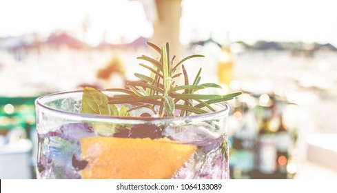 Gin cocktail on beach bar counter at sunset - Tropical, drinks, party and concept - Focus on rosemary