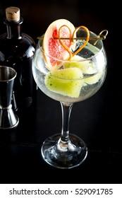 Gin drink cocktail fancy glass black background tonic water ice garnish fresh fruit craft cocktail cucumber orange peel decoration measure bottle lime peeler grapefruit room space for text