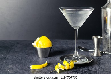 Gin Martini Cocktail With Lemon Twist On A Bar Table. Jigger in Background. Beverage Photography