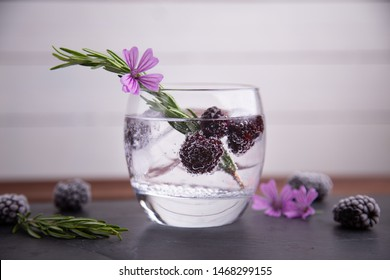 gin and tonic with blackberries, a sprig of rosemary and a flower of ornament