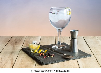 Gin Tonic with botanicals and bar spoon on wood table.