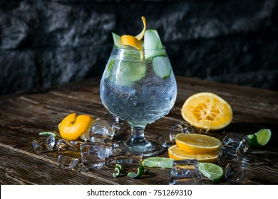 Gin tonic with a citric touch of lemon, orange and cucumber. Alcoholic drink.