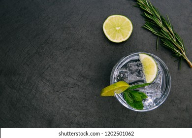 Gin tonic cocktail drink with ice glass green lime on dark background