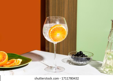 Gin tonic cocktail, garnished with orange slice, colorful background