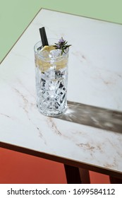 Gin tonic cocktail, with lemon and blooming rosemary, on a small table. Vintage aesthetic