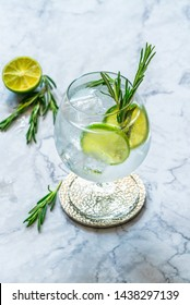 Gin and tonic cocktail with lime and rosemary - refreshing summer alkoholic drink