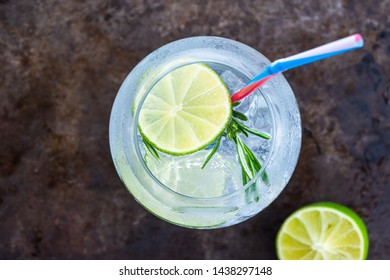 Gin and tonic cocktail with lime and rosemary - refreshing summer alkoholic drink - overhead view