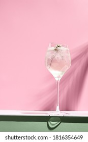 Gin tonic cocktail on pink and green background. Minimal pastel color concept. Sunlught and shadow tropic background