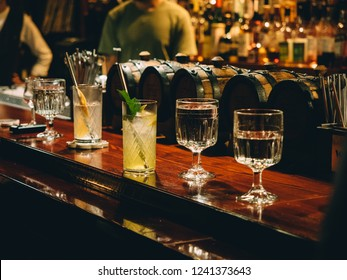 Gin tonic cocktails in glasses in bar stand.