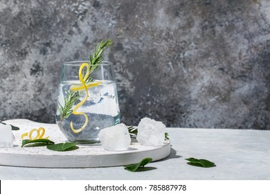 Gin and Tonic drink served with ice, lemon zest and fresh rosemary. Drink Concept. Copy space