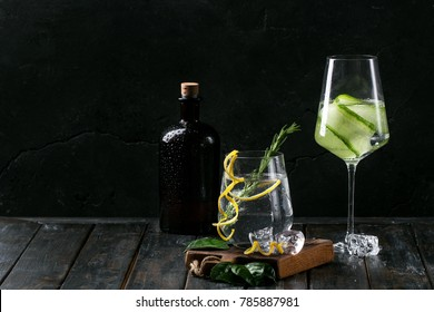 Gin and Tonic drink served with ice, lemon zest and fresh rosemary. Drink Concept. Dark Rustic style. Copy space