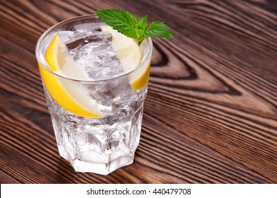 Gin tonic with ice in a glass on a wood background.