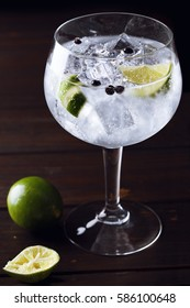 Gin tonic with ice, lime and juniper berry over a dark wood table