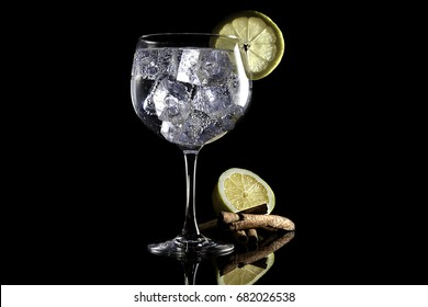Gin tonic with lemon and cinnamon on black background