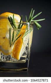 Gin with tonic, lemon and rosemary on  dark background.