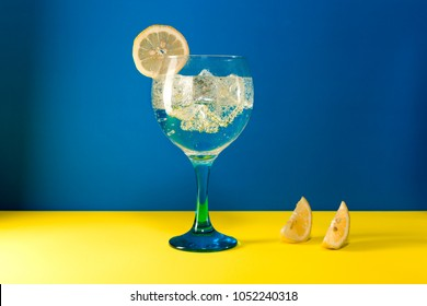 gin tonic with lemon slice and lemon segment  on blue and yellow background
