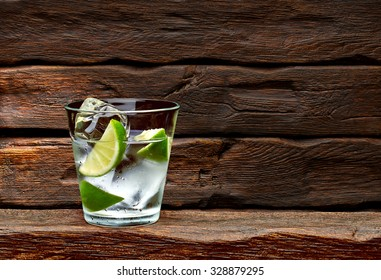 Gin tonic with lime wedges on wooden table and background