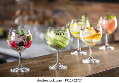 Gin tonic long drink as a classic cocktail in various forms with garnish in individual glasses such as orange, lemon, grapefruit, cucumber or berries.