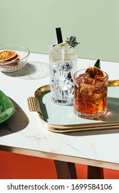 Gin tonic and Negroni cocktail, with charred orange, lemon slice and blooming rosemary, on a small table. Vintage aesthetic