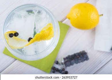 Gin and tonic on a highball glass with a lemon twist and juniper berries