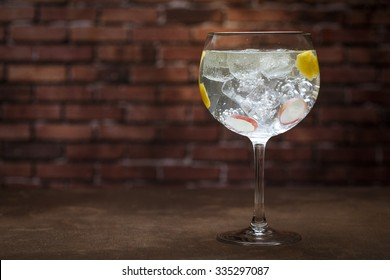 Gin and tonic on a wooden table with bricks background