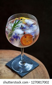 Gin and tonic with rosemary and borage flowers ice cubes