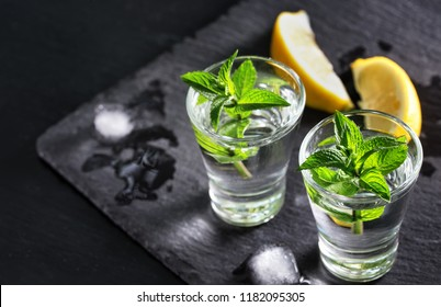 Gin or vodka with mint and ice. Two glasses with a cocktail of mint and ice alcohol with lemons on the black surface. Selective focus. Free space.