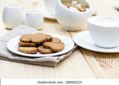 Ginger biscuits, cinnamon, a cup of hot coffee. Walnuts, hazelnuts on a wooden background