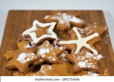 Ginger biscuits close up with sugar powder on a wooden board.