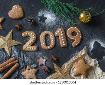 Ginger biscuits of the form of numbers and 2019 new year ginger cookies on dark background. Top view. Seasonal packaging and New Year's attributes
