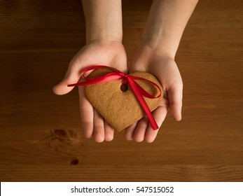 ginger biscuits in the shape of heart in children's palms