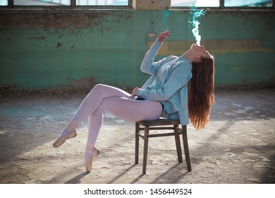 Ginger, blonde ballerina sitting on the chair smoking. Sport and smoking concept