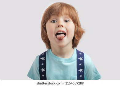 ginger boy is showing his tongue.bully, kid is teasing somebody. boasting. boy is in the otorhinolaryngologist room. boy is doing exercise with tongue to improve the speach