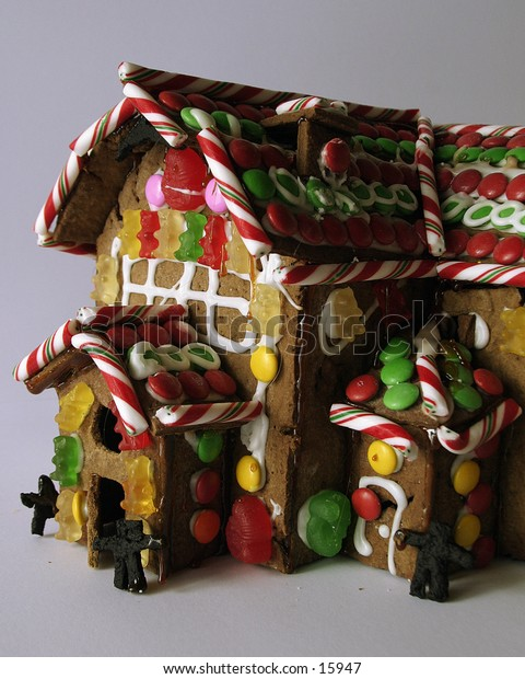 A ginger bread house seen from the front with little people standing in the doorway.