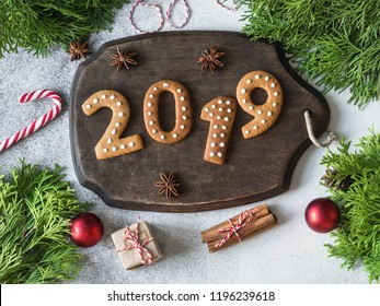 Ginger Christmas or New Year cookies in the form of numbers 2019 on a dark wood board on gray background. top view. Seasonal packaging and New Year's attributes