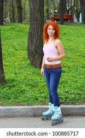 Ginger girl on roller skates listening to music in the park
