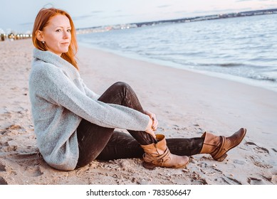 A ginger girl is sitting down close to the shore in Playa de Palma. She is wearing winter clothes and boots. Majorca, Spain. Balearic Islands.