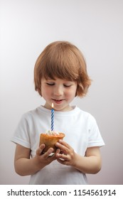 ginger good looking boy is making a wish in front of the cup cake on the isolated white background.secret