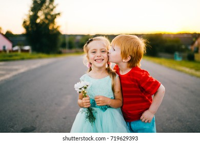 Ginger guy with pale skin kissing little shy beautiful girl in blue holiday dress outdoor on road in countryside at sunset on abstract background. Autumn in rural terrain. Funny sincere kids.