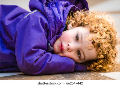 A ginger hair curly little girl laying on the floor in violet jacket looking at the camera. The kid is sad and concentrated, Spain, Barcelona, February 2014