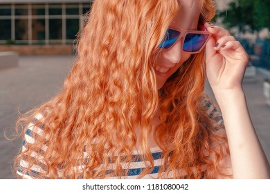Ginger haired girl in funny sunglasses looking away and down