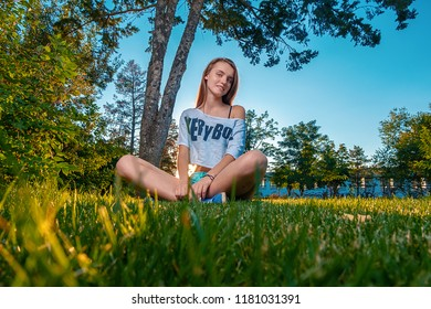 Ginger haired girl sitting on grass cross legged and looking in camera with cute smile on her face, a lot of copyspace on grass