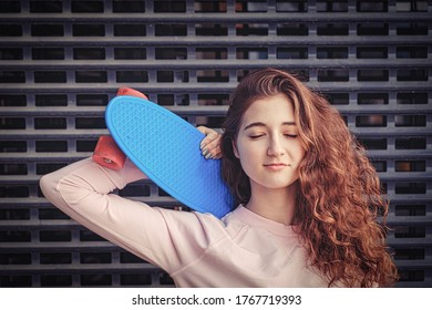Ginger haired lady daydreaming with her eyes closed. She is holding her blue pennyboard on her shoulder