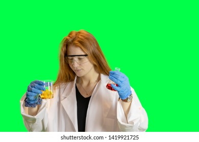 Ginger haired teen girl in lab coat with gloves and goggles holding beakers of colorful liquids.