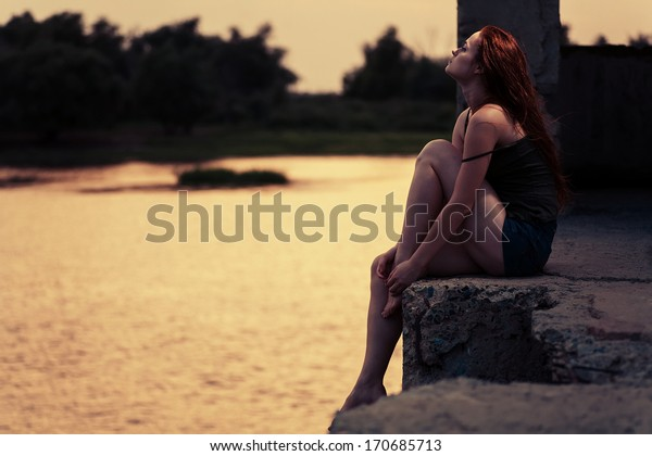 Ginger haired women looking up. Redhead women sitting near river in summertime and dreaming. Sunset light