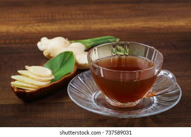 Ginger juice and fresh ginger with green leaves isolated on wooden background.