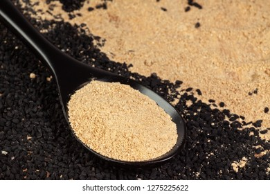Ginger powder in spoon on black cumin (nigella sativa or kalonji) seeds background
