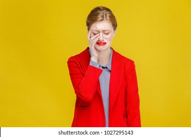 Ginger red head business woman in red suit have tooth pain. Studio shot, isolated on yellow background