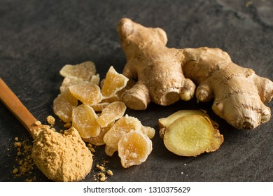 Ginger root, candied and ginger powder in wooden spoon over grey concrete background