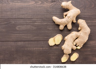 Ginger root on the wooden background. Top view.
